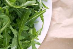 Frischer Arugula Eruca, eine kreuztragende Anlage und einfach Kohl Brassicaceae auf braunem Verpackungskraftpapier stockfoto