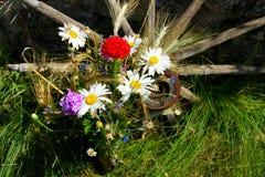 Frischer Blumenstrauß von Wildflowers auf dem alten hölzernen Rad Stockfotos