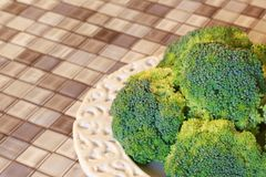 Frischer Brokkoli auf weißer Platte auf Tabelle lizenzfreie stockfotografie