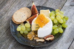 Frischer Camembert mit Honig, Trauben und Crackern auf einer Platte Lizenzfreies Stockbild