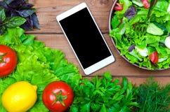 Frischer diätetischer Salat und Mobile auf einem Holztisch, Draufsicht heal stockfotos