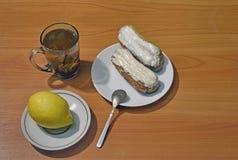 Frischer Eclair mit weißer Schokolade ein Tasse Tee und Zitrone jpg Lizenzfreie Stockfotografie