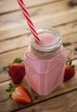 Frischer Erdbeeresmoothie in einem Glas Weißer hölzerner Hintergrund Hea stockfotos