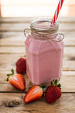 Frischer Erdbeeresmoothie in einem Glas Weißer hölzerner Hintergrund Hea stockbild