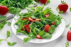 Frischer Erdbeersalat mit Arugula auf weißer Platte Stockfotografie