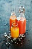 Frischer farbiger Juice Bottles auf Holztisch Lizenzfreie Stockfotografie