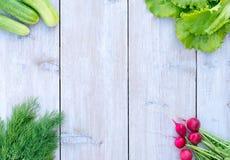 Frischer Frühlingskopfsalat, Frühlingszwiebeln und Dill, Gurkenrettiche auf einem hellen hölzernen Hintergrund saftig, Gemüse, Vi Lizenzfreie Stockfotografie