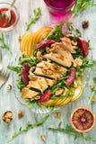 Frischer Frühlingssalat mit der gegrillten Hühnerbrust, Arugula, Birne und orange Scheiben und Walnüsse Stockfotografie