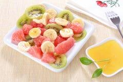 Frischer Fruchtsalat auf weißer Platte mit Honig stockfotos
