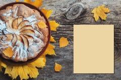 Frischer Gebäckapfelkuchen Charlotte auf dem Holztischhintergrund verziert mit gelbem Herbstlaub Fall-Lebensmittel-Koch Cuisine H Lizenzfreie Stockfotografie