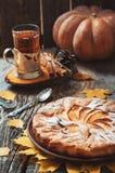 Frischer Gebäckapfelkuchen mit Zuckerpulver auf Holztisch mit heißem Getränktee und -zimt auf Hintergrund Selbst gemachte Kuchen  Stockbilder