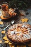 Frischer Gebäckapfelkuchen mit Zuckerpulver auf Holztisch mit heißem Getränktee und -zimt auf Hintergrund Selbst gemachte Kuchen  Stockfotos