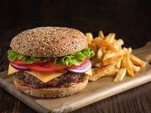 Frischer geschmackvoller Burger und Kartoffeln auf hölzernem Brett Stockfotografie
