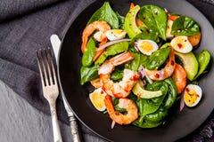 Frischer, gesunder Salat mit Garnelen, Spinat und Avocado auf einem blac Lizenzfreie Stockbilder