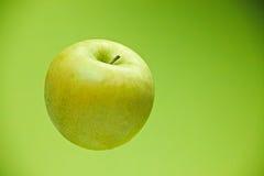 Frischer grüner Apfel auf grünem Hintergrundhintergrund Stockbild