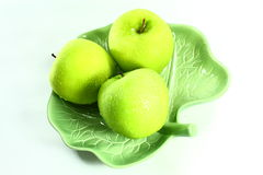 Frischer grüner Apfel auf grünem Teller stockfotografie
