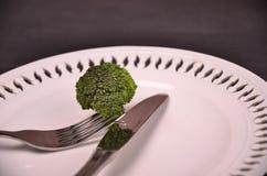 Frischer grüner Brokkoli auf weißer Platte über hölzernem Hintergrund Stockbild