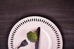 Frischer grüner Brokkoli auf weißer Platte über hölzernem Hintergrund Stockfoto