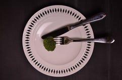 Frischer grüner Brokkoli auf weißer Platte über hölzernem Hintergrund Stockfotos