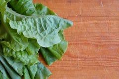 Frischer grüner Kopfsalat auf einem hölzernen Hintergrund Lizenzfreie Stockbilder