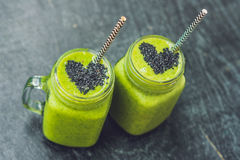 Frischer grüner Smoothie mit Banane und Spinat mit Herzen von Samen des indischen Sesams Liebe für ein gesundes rohes Lebensmitte Stockfotos