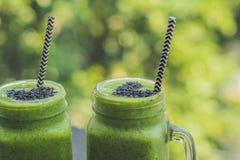 Frischer grüner Smoothie mit Banane und Spinat mit Herzen von Samen des indischen Sesams Liebe für ein gesundes rohes Lebensmitte Stockfotografie
