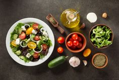 Frischer griechischer Salat in der Platte und in den Bestandteilen Stockbild