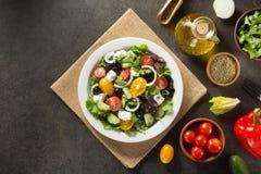 Frischer griechischer Salat in der Platte und in den Bestandteilen Lizenzfreies Stockfoto