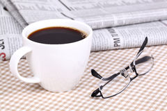 Frischer heißer Kaffee auf Zeitung Stockfotos