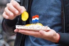 Frischer Hering mit Zwiebel- und netherlandflagge im Mann übergibt Nahaufnahme Traditionelles niederländisches Lebensmittel stockbilder