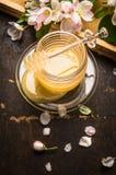 Frischer Honig im Glas mit Blumen und Bienenwabe auf hölzernem Hintergrund Stockfotografie