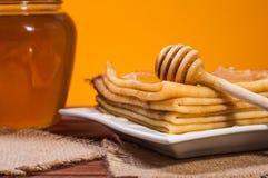 Frischer Honig mit einem Stapel Blinis oder Krepps Lizenzfreie Stockbilder