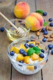 Frischer Hüttenkäse mit Pfirsich, Blaubeere, Mandeln und Honig Stockbilder