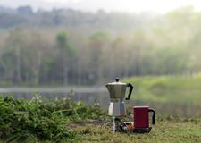 Frischer Kaffee auf einem kleinen Gasherd und rosa Kaffeetassen auf grünem Gras für ein Abenteuer mit Ansichten der Berge und der stockfotografie