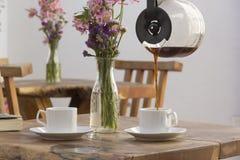 Frischer Kaffee wird in eine Schale in einem äußeren Restaurant gegossen stockfotos