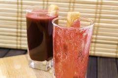 Frischer Karotten- und Wurzel-Saft im Glas, das mit Karottenscheiben man verziert wird, ist auf dem hölzernen selektiven Behälter Lizenzfreie Stockbilder