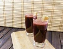 Frischer Karotten- und Wurzel-Saft im Glas verziert mit Karottenscheiben auf dem hölzernen selektiven Fokus des Behälter- und Bam Lizenzfreie Stockfotos