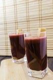 Frischer Karotten- und Wurzel-Saft im Glas verziert mit Karottenscheiben auf dem hölzernen selektiven Fokus des Behälter- und Bam Stockfoto