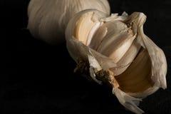 Frischer Knoblauch schneidet dunkles Foto auf schwarzer Hintergrundnahaufnahme Lizenzfreie Stockfotos