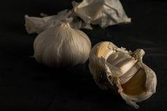 Frischer Knoblauch schneidet dunkles Foto auf schwarzer Hintergrundnahaufnahme Lizenzfreie Stockfotografie