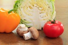 Frischer Kohl, Pilze, Pfeffer und Tomate auf dem Tisch Stockfotos