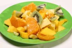 Frischer Obstsalat auf einer grünen Platte Lizenzfreies Stockfoto