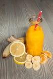 Frischer orange Smoothie mit Banane und Zitrone in einer Flasche Stockfotos