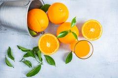Frischer Orangensaft und Orange in einem Korb auf einem weißen hölzernen BAC stockbilder