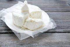Frischer organischer handgemachter Käse, der im Seihtuch und in der Weinleseplatte hängt Lizenzfreies Stockbild