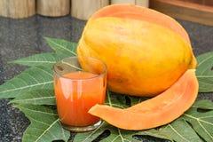 Frischer Papayasaft im Glas mit Papayafrüchten, -blatt und -scheiben Lizenzfreies Stockbild