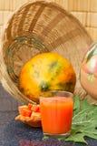 Frischer Papayasaft im Glas mit Papayafrüchten, -blatt und -scheiben Stockbild
