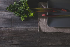 Frischer Rhabarber auf grauer Platte und altem Holztisch, flache Lage Stockfotos
