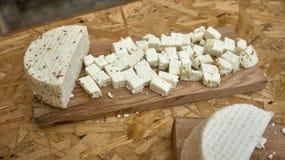 Frischer roher gealterter Delikatessenkäse mit Fenchel an Bord für den Schnitt des Käses auf Holztisch lizenzfreie stockbilder