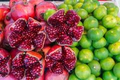 Frischer Saft des bunten roten Granatapfels und der grünen Zitrone von den Tropen Stockbild